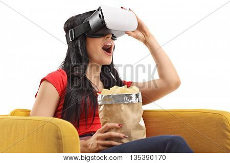 Joyful young woman looking in VR goggles and eating potato chips isolated on white background