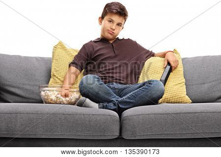 Bored little boy watching TV and eating popcorn seated on a gray sofa isolated on white background