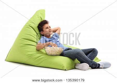 Pensive little boy eating popcorn seated on a green beanbag isolated on white background