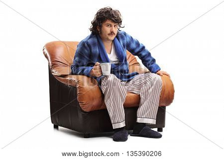 Grumpy man sitting in an armchair and drinking his morning coffee isolated on white background
