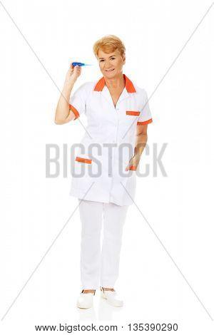 Smile elderly female doctor or nurse holding thermometer