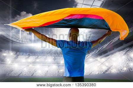 Sporty man holding a German flag against sports arena
