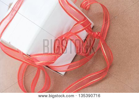 Gift box with red ribbon on wood