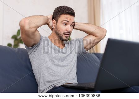 Man read bad news on laptop big eyes frightened expression
