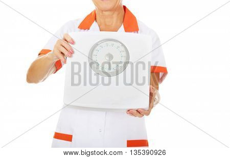 Elderly female doctor or nurse holds weigh scale