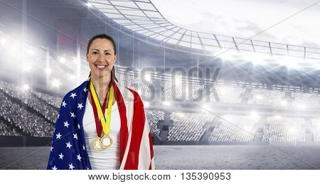 Athlete posing with american flag and gold medals around his neck in a stadium