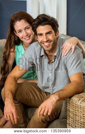 Portrait of young couple embracing in living room