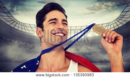 Athlete holding gold medal after victory against stadium