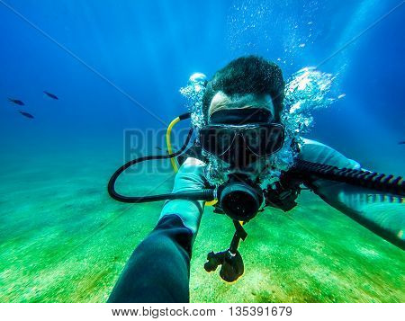 Man taking a photo of himself, while floating in the water for scuba diving.