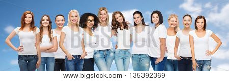 friendship, diversity, body positive and people concept - group of happy women of different age size and ethnicity in white t-shirts hugging over blue sky and clouds background