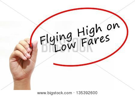 Man Hand writing Flying High on Low Fares with marker on transparent wipe board. Business, internet, technology concept.