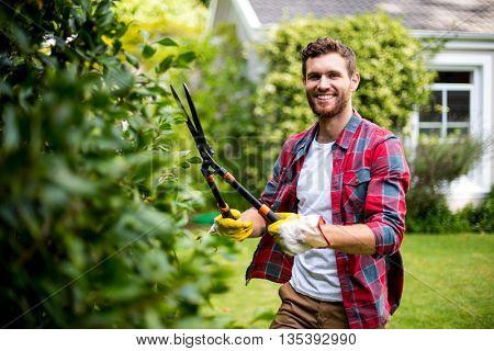 Happy gardener cutting plants in yard