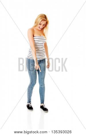 Young woman pointing down. Isolated on white.