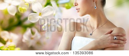beauty, jewelry, people and luxury concept - beautiful asian woman or bride with earring, finger ring and pendant over natural spring lilac blossom background