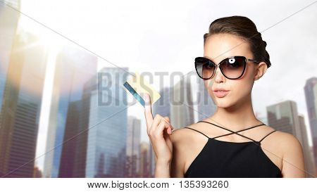 shopping, finances, fashion, people and luxury concept - beautiful young woman in elegant black sunglasses with credit card over city skyscrapers background
