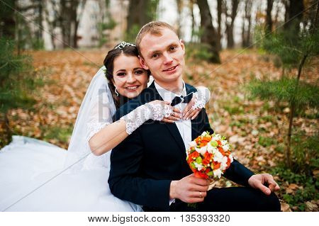 Happy Wedding Couple Sitting At Autumn Forest With Fell Leaves From The Trees