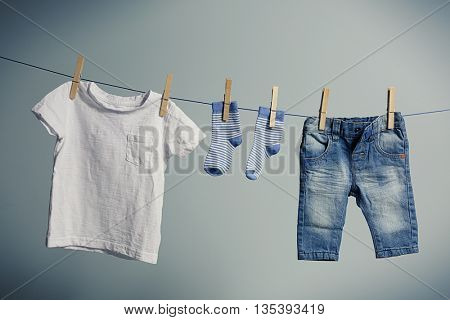 Baby clothes hanging on rope on grey background