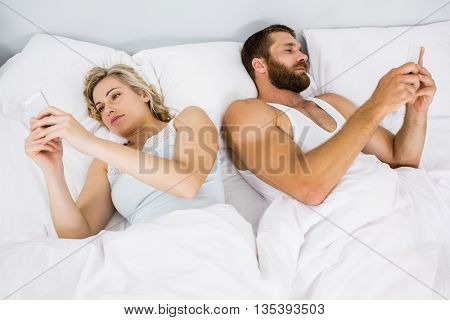 Couple using mobile phone on bed at bedroom