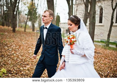 Happy Wedding Couple At Autumn Forest With Fell Leaves From The Trees