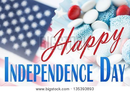 anniversary, celebration, patriotism and holidays concept - close up of glazed sweet candies with american flag at 4th july theme party with happy independence day words