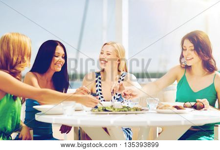 summer holidays and vacation - girls in cafe on the beach
