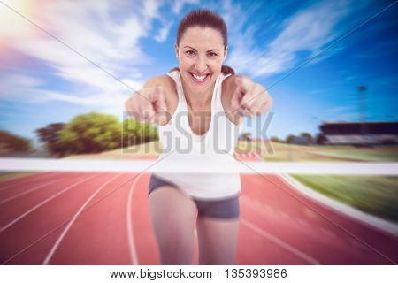 Female athlete posing on white background against high angle view of track