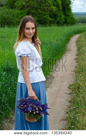 Beautiful girl with basket of lupine flowers on rural road near green field