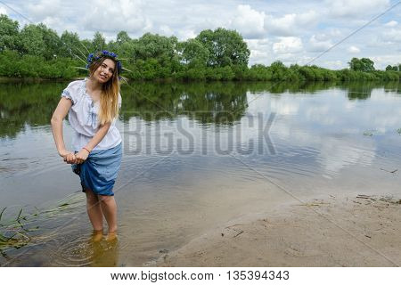 Beautiful young woman in wreath from cornflowers on river bank squeezes wet hem of her skirt