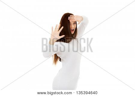 Scared young woman trying to hide and defend herself