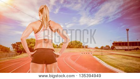 Female athlete posing with hands on hip against high angle view of track