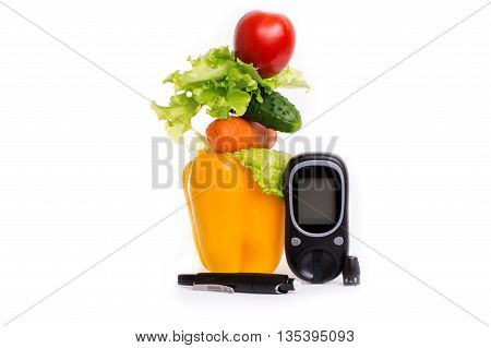 healthy organic food and a glucometer on a white background