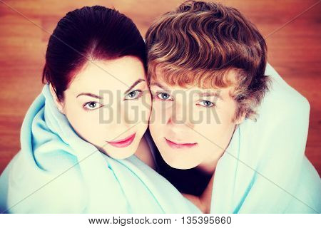 Young couple wrapped in blue blanket.