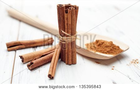 Ground Cinnamon In Wooden Spoon And Cinnamon Sticks On White Background