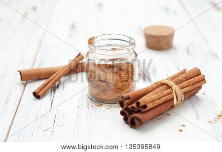 Ground Cinnamon And Cinnamon Sticks On White Background