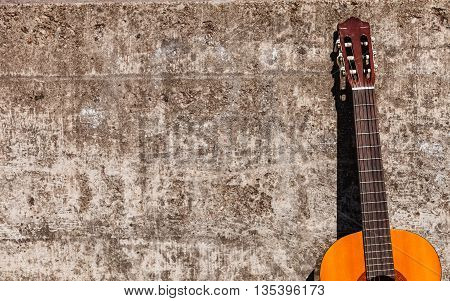 Music sound recreation passion concept. Guitar leaning on wall. Instrument standing outside.