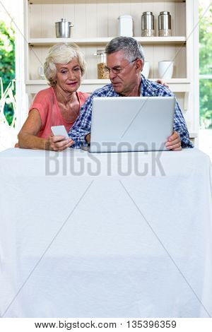 Senior couple using laptop and mobile phone in kitchen at home
