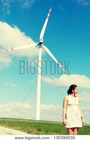 Happy teen girl next to wind turbine.