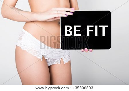 technology, internet and networking - close-up ass of girl in lacy lingerie, holding a tablet pc with be fit sign. Adult content.