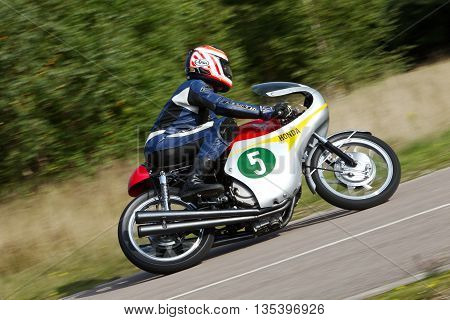 EELMORE, UK - SEPTEMBER 29: An unnamed rider driving a vintage Honda 900cc motorcycle exits a sharp left hand corner during the VMCC Eelmore sprint competition on September 29, 2013 in Eelmore