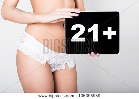 technology, internet and networking - close-up ass of girl in lacy lingerie, holding a tablet pc with twenty-one plus sign. Adult content.