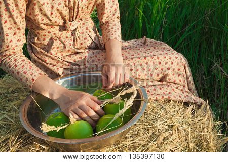 The healthy rural life. The woman sitting on a haystack with apples against green meadow