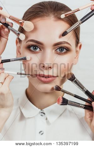 Closeup portrait of beautiful young woman with makeup brushes.