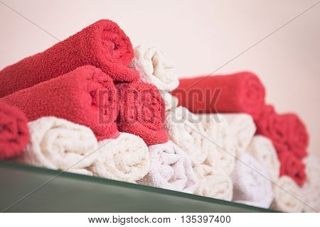 Big bunch of red and white towels in bathroom shelf or hairdressing salon or beauty salon.