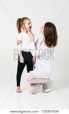 Doctor examining throat of little girl on the white background