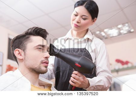Closeup portrait of hairdresser drying handsome man's hair by hair dryer in hairdressing salon. Man looking in mirror.