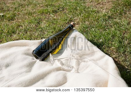 Champagne bottle and glasses on white blanket