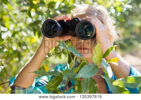 Close up of a woman looking on binoculars on the wood