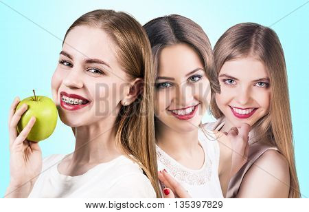 Young women with teeth braces and healthy smile eats green apple over blue background