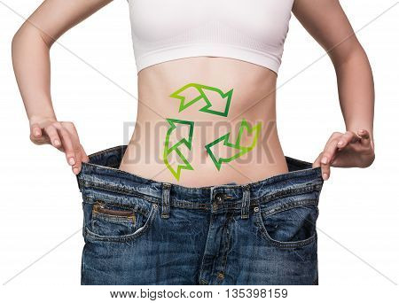 Woman holding big jeans with drawing arrows on her belly isolated on white