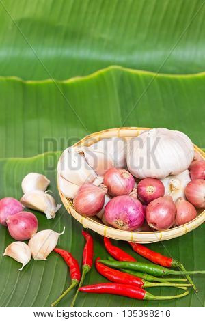 Red onion and garlic in wicker basket on banana leaves background